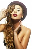 Sexy provocative blond woman with long wavy hair puckering her red lips at the camera for a kiss as she holds on to her stylish hat isolated on white