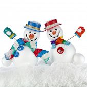 Two Cheerful dancing snowmans in a striped scarfs, mittens and cylinder hat isolated on white backgr