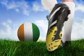 Composite image of football boot kicking ivory coast ball against field of grass under blue sky