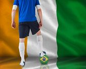 Handsome football player in blue jersey against ivory coast national flag