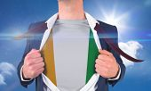 Businessman opening shirt to reveal ivory coast flag against bright blue sky with clouds