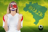 Excited costa rica fan in face paint cheering against football pitch with brazil outline and text