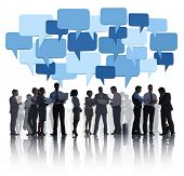 Group Of Business People Discussing And Blue Speech Bubbles Above Them.