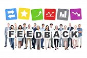 Group Of Business People Holding The Word Feedback And Related Symbols Above