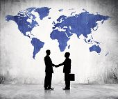 Two Business Men Shaking Hands And A Blue Cartography Of The World Above.