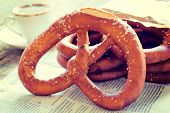 stock photo of pretzels  - Traditional Bavarian pretzel on the newspaper and cup of coffee in background - JPG
