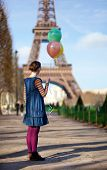 Girl In Bright Clothes With Colourful Balloons In Paris Near The Eiffel Tower