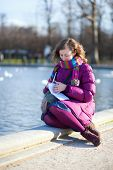 Pretty Young Girl Writing Something In Her Notebook Outdoors