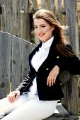 Elegant woman in costume for  horseback riding outdoors