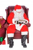 Santa enjoying a rest after a nights work, sitting and eating some cookies