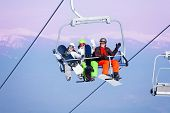 pic of ropeway  - Three excited young people with snowboarders sitting on ropeway on the mountains background - JPG