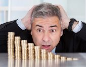 Surprised Businessman With Stack Of Coins