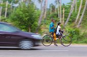 WELIGAMA, SRI LANKA - MARCH 7, 2014: Couple riding a bicycle on local road. Tourism and fishing are