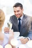 restaurant, couple and holiday concept - smiling man with glass of champagne looking at wife or girl
