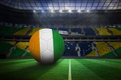 Football in ivory Coast colours in large football stadium with brasilian fans