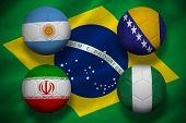 Composite image of group f footballs for world cup against digitally generated brazilian national fl