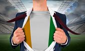 Businessman opening shirt to reveal ivory coast flag against large football stadium with lights