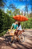 Lovely Young Couple Riding And Kissing On The Bicycle With Red Dirigible And The Basket Full Of Bagu
