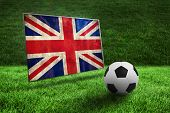 Black and white football on grass against union jack flag in grunge effect