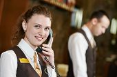 Happy female receptionist worker with phone standing at hotel counter