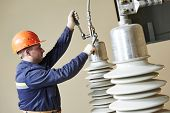 Electrician lineman repairman worker at huge power industrial transformer installation work