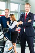 Seller or car salesman and clients or customers in car dealership presenting the interior decoration