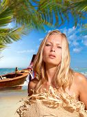 Beautiful woman on the beach in Thailand with long tailed boat on background