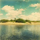 Coast of river under blue sky with white clouds in grunge and retro style.