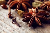 Stars anise with cardamom and carnation on wooden background