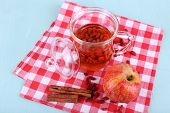 Goji berries drink in glass cup, ripe apple and cinnamon on red checkered napkin on light blue wooden background