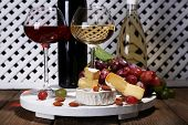 Supper consisting of Camembert cheese, wine and grapes on stand on wooden table on white fence background