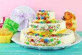 Beautiful tasty birthday cake and gifts on color background