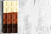 Milk chocolate bar on color wooden background