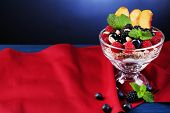 Healthy breakfast - yogurt with  fresh fruit, berries and muesli served in glass bowl on color wooden table, on dark color background