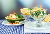 Tasty salads with shrimps and avocado in glass bowl and on plate, on table, on bright background