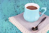 Cup of coffee with napkin on wooden table