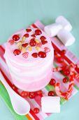 Raspberry milk dessert in glass jar, on color wooden background