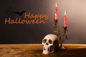 Bloody candles for Halloween holiday and decorative skull on wooden table, on dark background