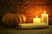 Halloween decoration with spider on web, paper roll, pumpkin and candles on wooden background