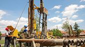 stock photo of rig  - Drilling Rig Workers Operating Machinery - JPG