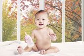 Baby Playing On Bed With Milk Bottle