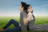 Couple Sitting And Holding Hands On Park