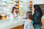 Cheerful pharmacist chemist woman giving vitamins to child girl in pharmacy drugstore