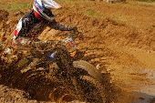 stock photo of mud  - Motocross biker riding through the dirty puddle splashing drops of mud - JPG