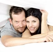 Couple In Love Smiling Under Bed Sheet