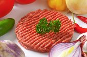 raw beef burger surrounded with fresh vegetable