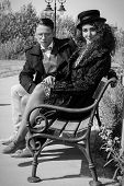 Young Fashion Elegant Stylish Retro Couple Sitting On Bench