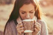 picture of hot-weather  - Woman wearing warm knit clothes drinking cup of hot tea or coffee outdoors in sunlight - JPG