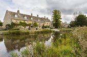 image of slaughter  - Stream running through the picturesque Cotswold village of Lower Slaughter Gloucestershire England