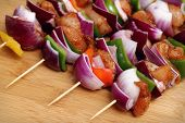 Homemade Chicken and Bacon Skewers Kebabs with Peppers Onions and Herb Marinate on wooden background
